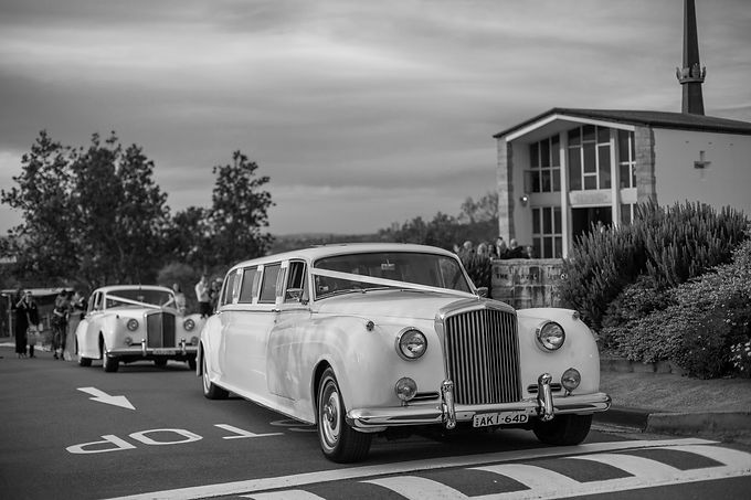 After the ceremony. Bride and groom driving away in the wedding cars. Bride and groom at the wedding ceremony at HMAS Watson Chapel. Wedding photography by best Sydney wedding photographer, Grant Hoskinson Photography.