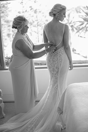 Mother of the bride helping to dress the bride. Doing up the buttons on the back of the wedding dress .Wedding photography by best sydney wedding photographer, Grant Hoskinson Photography.