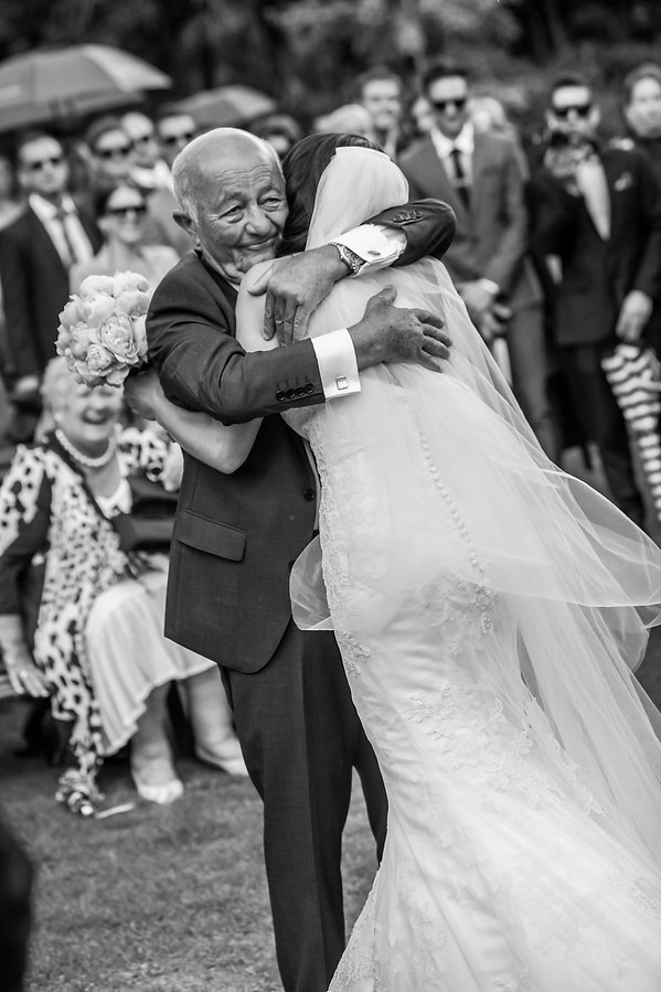 Beautiful wedding photography by popular wedding photographer, Grant Hoskinson Photography. Father of the bride hugging the bride after walking the bride down the aisle.Groom with groomsmen.  Royal Botanic Gardens, Melbourne.