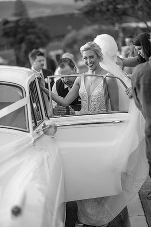 After the ceremony. Bride entering the car. Bride and groom at the wedding ceremony at HMAS Watson Chapel. Wedding photography by best Sydney wedding photographer, Grant Hoskinson Photography.