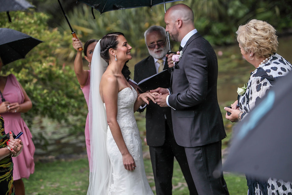 Beautiful wedding photography by popular wedding photographer, Grant Hoskinson Photography. Groom putting the wedding ring on the brides finger during wedding ceremony.Groom with groomsmen.  Royal Botanic Gardens, Melbourne.
