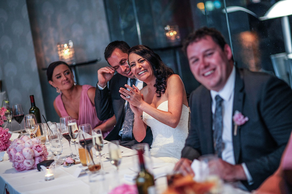 The bride during the groom's speech at the wedding reception at River's Edge Events wedding venue. Beautiful wedding photography by popular Sydney wedding photographer, Grant Hoskinson Photography.