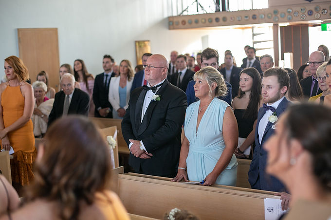 Parents of the bride at the wedding ceremony at HMAS Watson Chapel. Wedding photography by best Sydney wedding photographer, Grant Hoskinson Photography.
