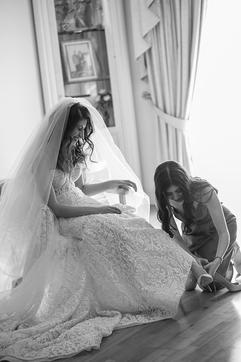 Bridesmaid helping the bride to put on her wedding shoes. Photography by best Sydney wedding photographer Grant Hoskinson Photography.