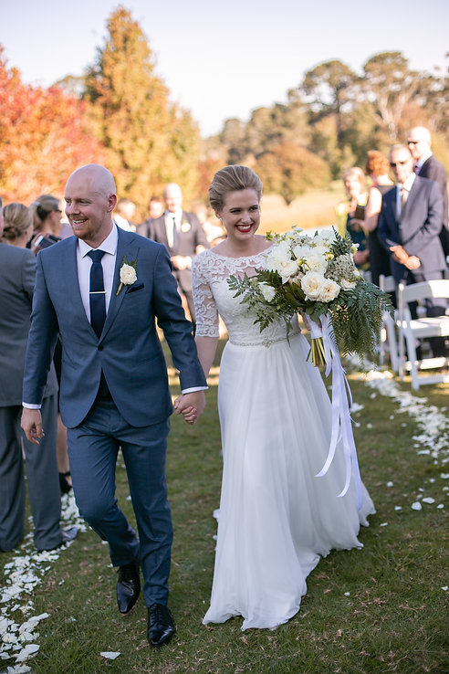 Bride and groom walking back up the aisle at outdoor wedding ceremony at Gibraltar Hotel, Bowral. Wedding photography by best sydney wedding photographer, Grant Hoskinson Photography.