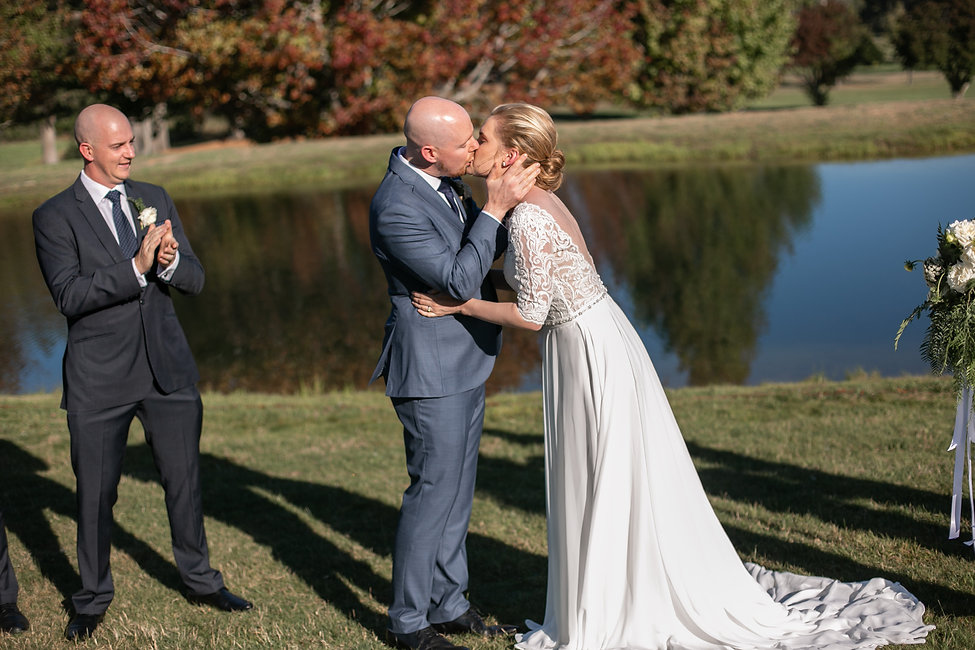 Kiss the bride at outdoor wedding ceremony at Gibraltar Hotel, Bowral. Wedding photography by best sydney wedding photographer, Grant Hoskinson Photography.