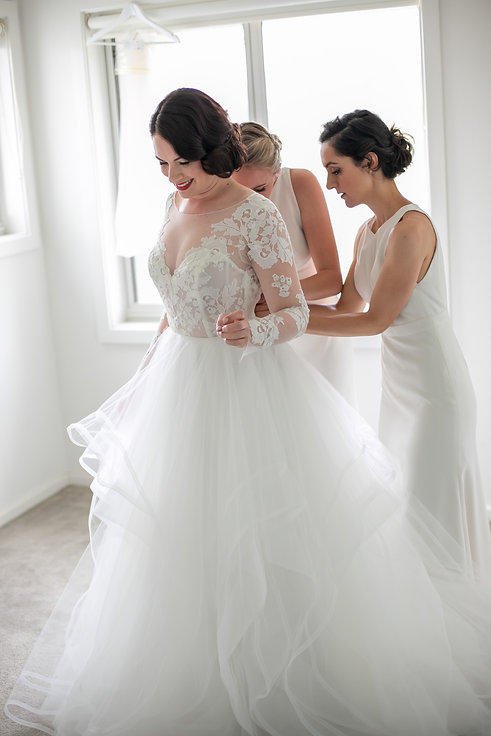 Bride putting on the wedding dress with the bridesmaids helping her. Bride getting her hair and makeup done. Wedding Dress. Wedding photography by best sydney wedding photographer, Grant Hoskinson Photography.