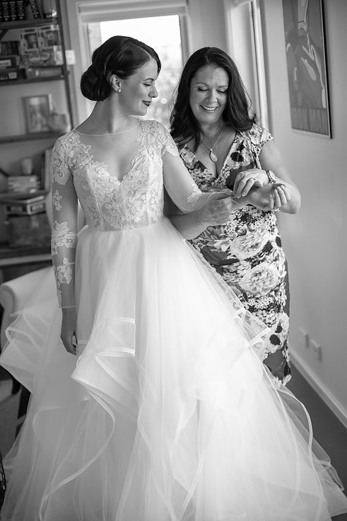 Mother of the bride helping to dress the bride. Wedding photography by best sydney wedding photographer, Grant Hoskinson Photography.
