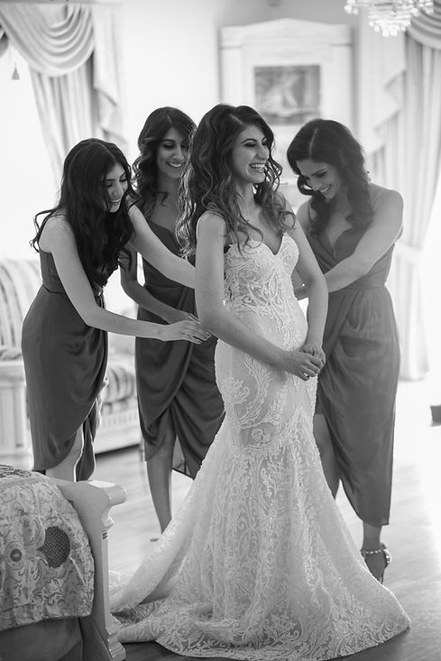Bride putting her wedding dress on helped by the bridesmaids. Photography by best Sydney wedding photographer Grant Hoskinson Photography