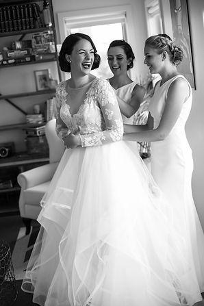 Bridesmaids helping the bride put her wedding dress on. Wedding photgraphy by Sydney wedding photographer Grant Hoskinson Photography.