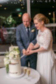 Bride and groom cutting wedding cake at wedding reception at Gibraltar Hotel, Bowral. Wedding photography by best sydney wedding photographer, Grant Hoskinson Photography.