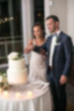Cuting the wedding cake. Wedding reception. Sugar Beach Events. Maui, Hawaii.