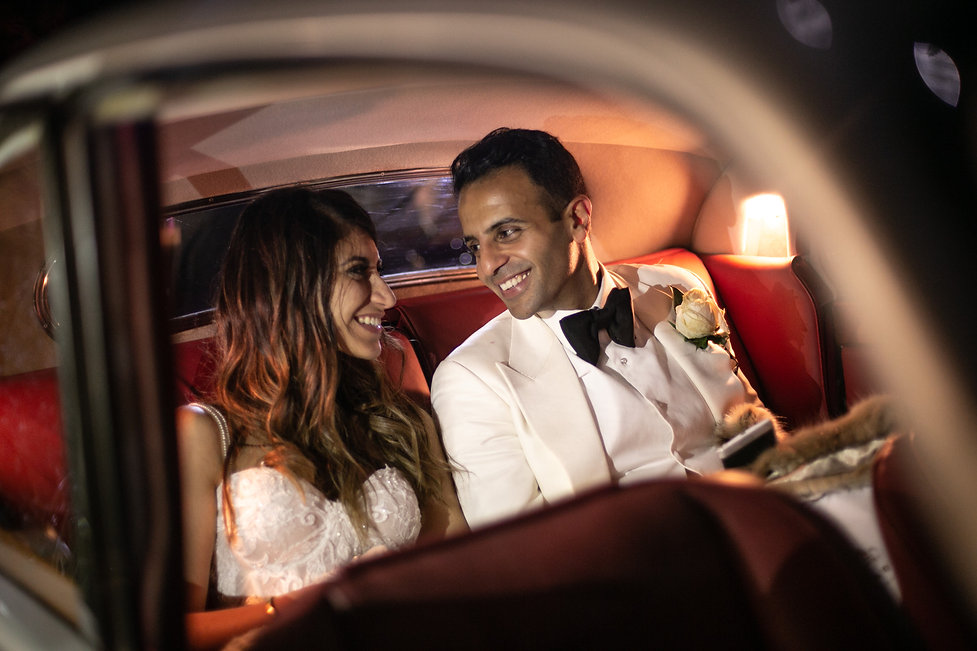 Bride and groom in wedding car leaving reception. Wedding reception at Sergeants Mess. Photography by best Sydney wedding photographer Grant Hoskinson Photography.
