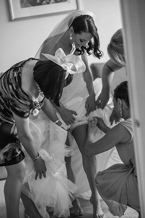Beautiful wedding photography by popular wedding photographer, Grant Hoskinson Photography. Bride puttingonthe garter with bridesmaids