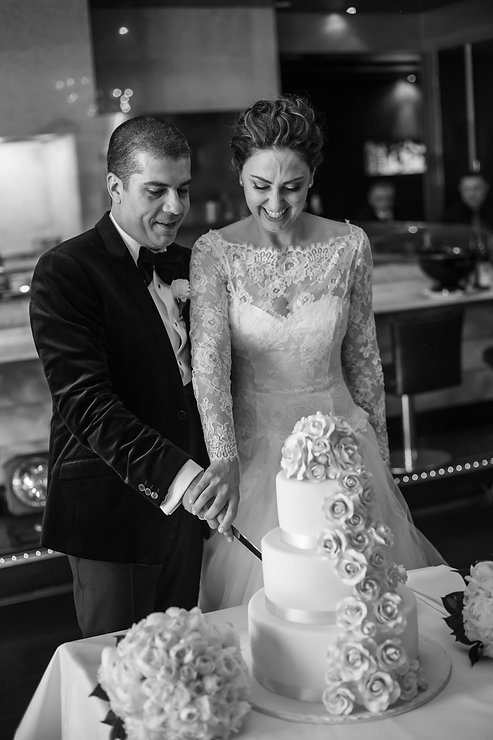Cutting the cake at the wedding reception venue at Quay Restaurant. Wedding photography by best sydney wedding photographer, Grant Hoskinson Photography.