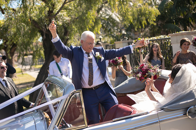Father of the bride dancing in the wedding car on the way to the church for the wedding ceremony. Photography by best Sydney wedding photographer Grant Hoskinson Photography.