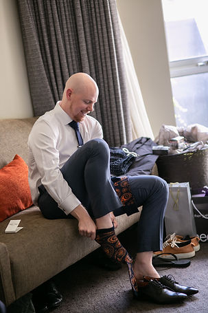 Groom putting on his shoes at Gibraltar Hotel, Bowral. Wedding photography by best sydney wedding photographer, Grant Hoskinson Photography.