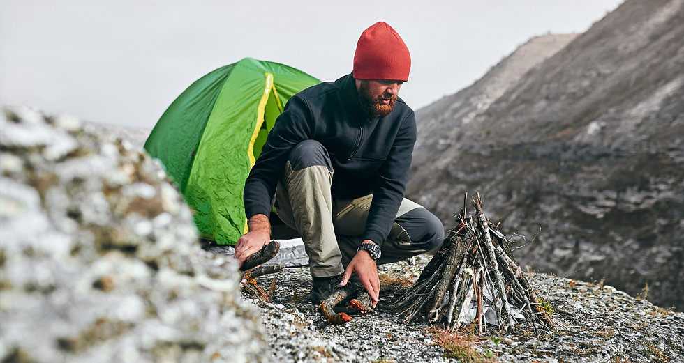 male setting up camp fire on mountain to