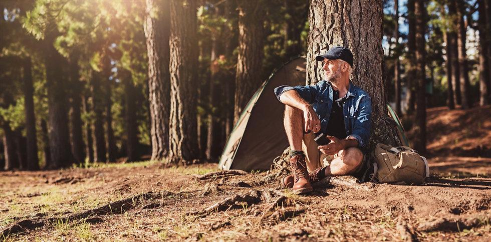 older male sitting by tree in woods.jpg