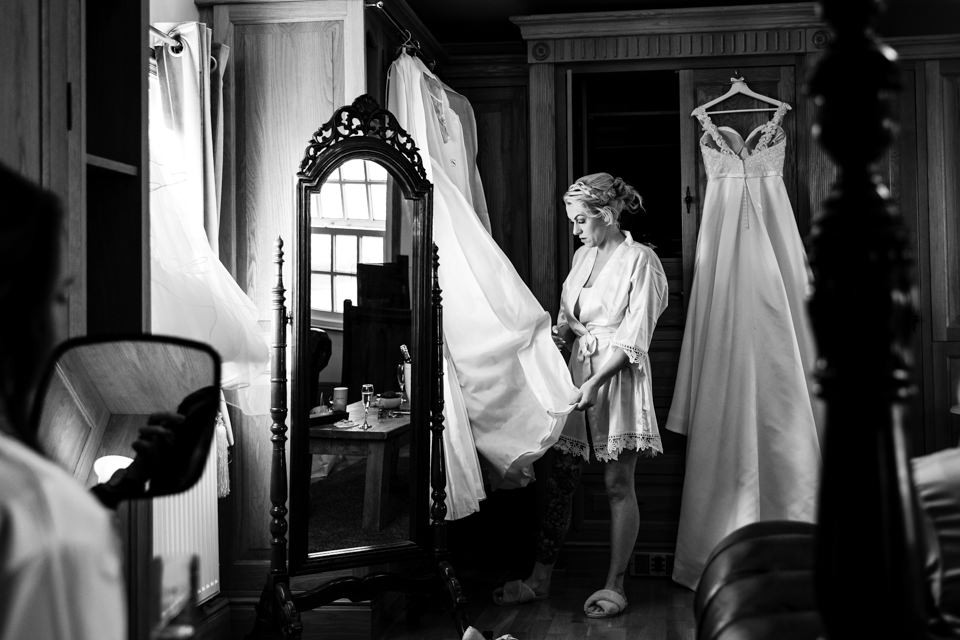 Photo of a bridesmaid getting out the dresses that are hanging on the cupboards.