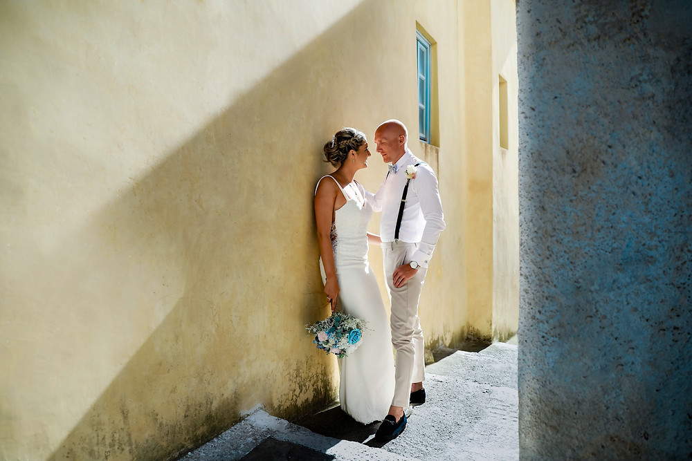 Photo of a bride and groom on their destination wedding to Santorini,  standing by a yellow wall.