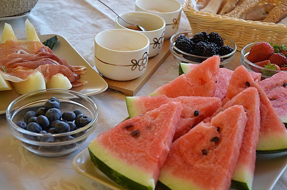 Dettaglio della colazione in giardino presso B&B Melograno MC. Anguria, mirtilli, more, melone con prosciutto crudo, zucchero