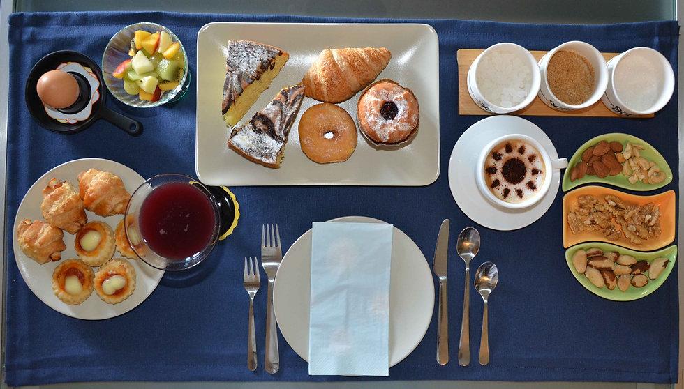 Colazione servita al tavolo presso bed and breakfast Melograno MC. Caffè, uova, frutta, dolci fatti in casa, zucchero e spremuta