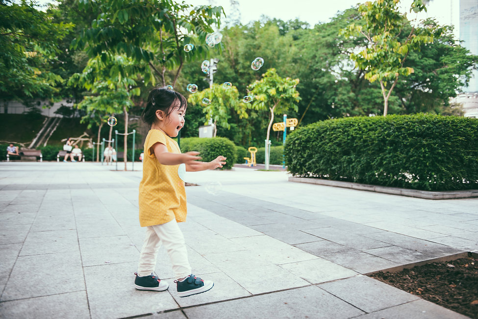 Toddler Girl Chasing Bubbles