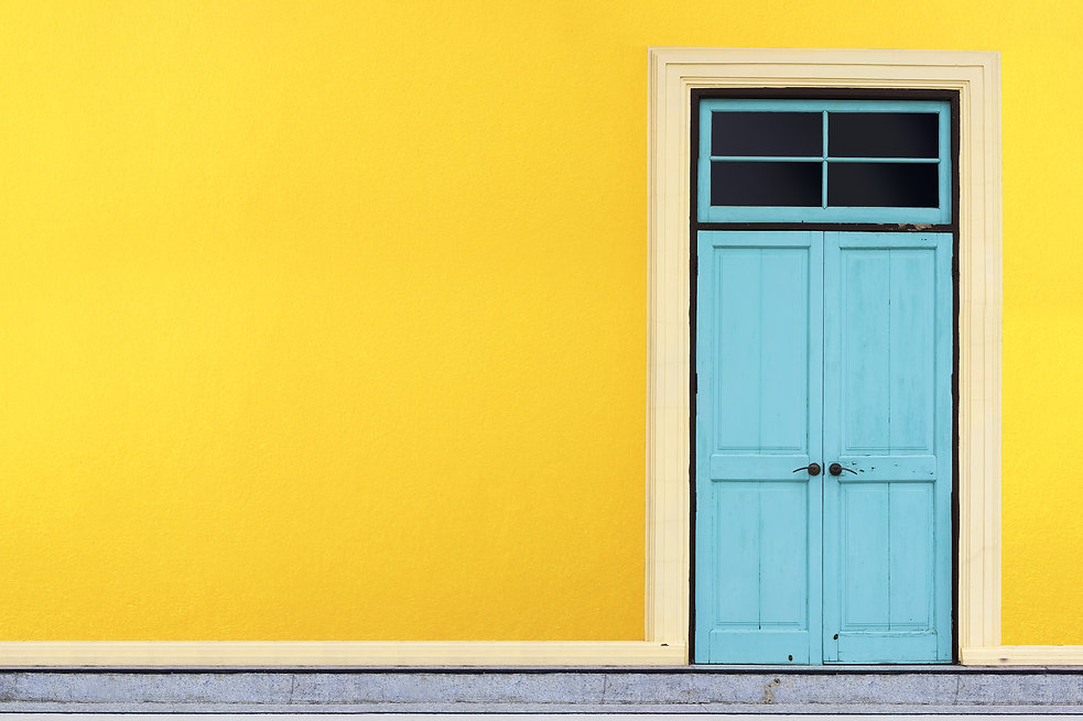 Closed blue wooden door on yellow wall b