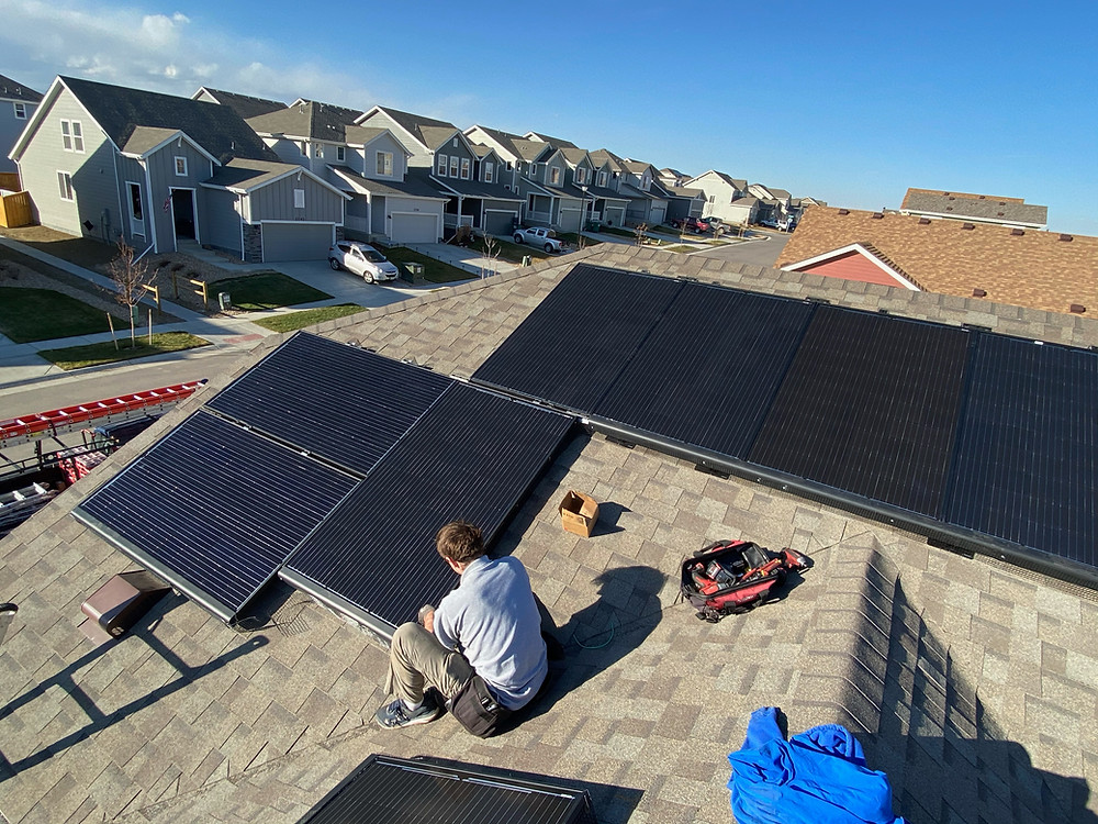 solar panels being installed on a suburban roof