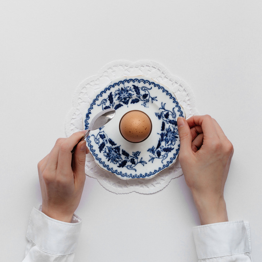 Person holding a spoon and a dish with a boiled egg.