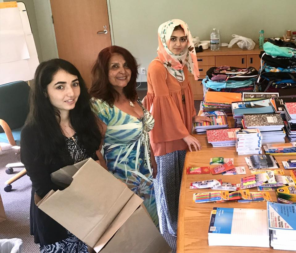 Sapida Barmaki (Montclair State 2019), Latifa Woodhouse, and Shahrzad Ahmadi (Montclair State 2021) assembling backpacks for Long Island children in need