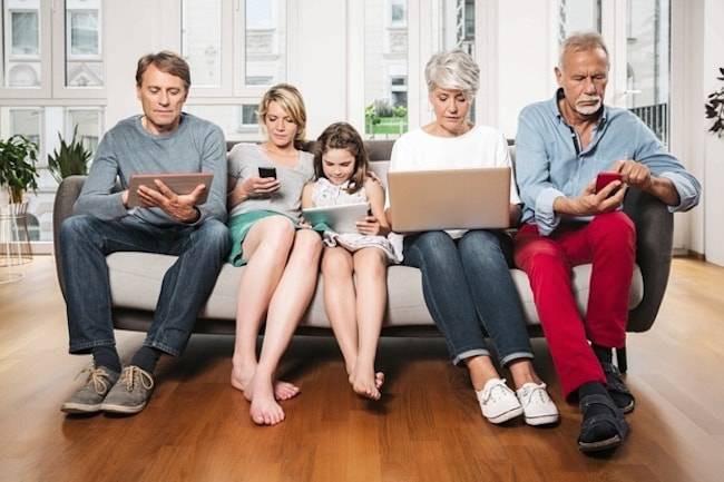Família sentada num sofá. Pai, mãe, filha e avós. Todos olhando para baixo, cada um conectado em seu próprio aparelho eletrônico.