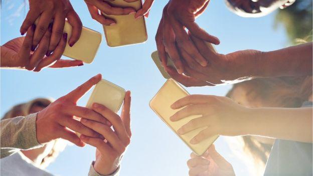 Foto de várias pessoas em roda utilizando smartphones, com plano detalhe para as mãos.