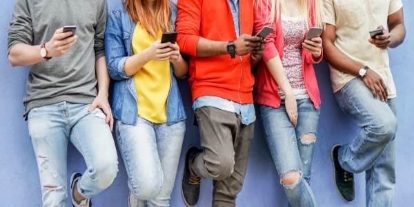 Jovens encostados no muro, cada um checando seu próprio celular