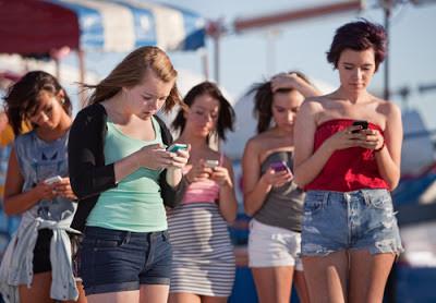 Grupo de cinco mulheres utilizando o celular.