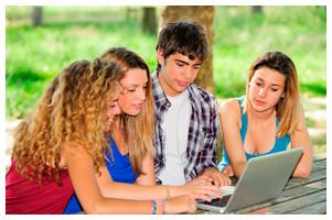 Grupo de quatro jovens se relacionando em frente ao computador.