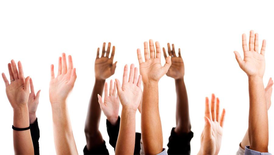 Diversos braços levantados com as mãos abertas