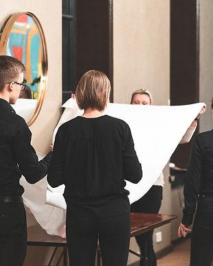 Tarjoilijat kattavat pöytää Helsingin Valkoisessa Salissa häitä varten.