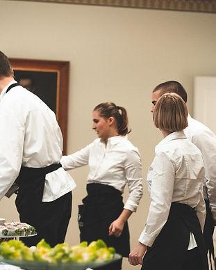 Tarjoilijat valmistelevat ruokaa häävieraita varten pitopalvelun kanssa Helsingin Valkoisessa Salissa.
