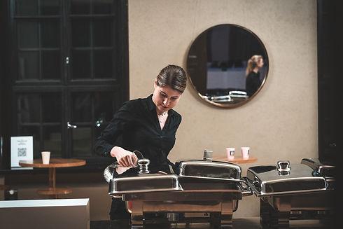 Tarjoilija kaatamassa vettä lämmitysalustaan Valkoisessa Salissa Helsingissä.
