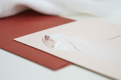 Painted wedding invitations with a white and brown swash and red envelopes