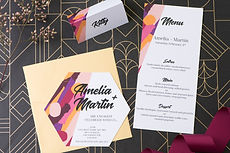Bold and vibrant purple and pink hexagon shaped engagement invitations with matching menu and tent place card