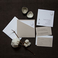 Natural stone minimalist wedding invitations with white and brown inclusion cards and a double circle moon graphic and unique paper sleeve