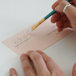 Designer hand painting the rsvp card in a wedding invitation suite