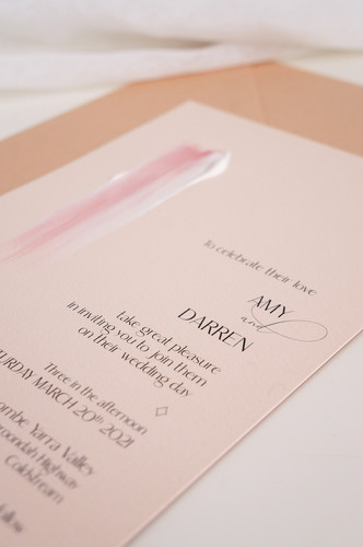 Pink and white painted wedding invitations on peach card with a soft brown envelope