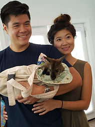 A couple poses for a picture with a baby wallaby from the Roos2u ranch in Germantown, Maryland