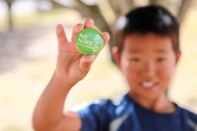 """Natsuki dimostra un badge scritto""""NO Nuke Fukushima"""""""