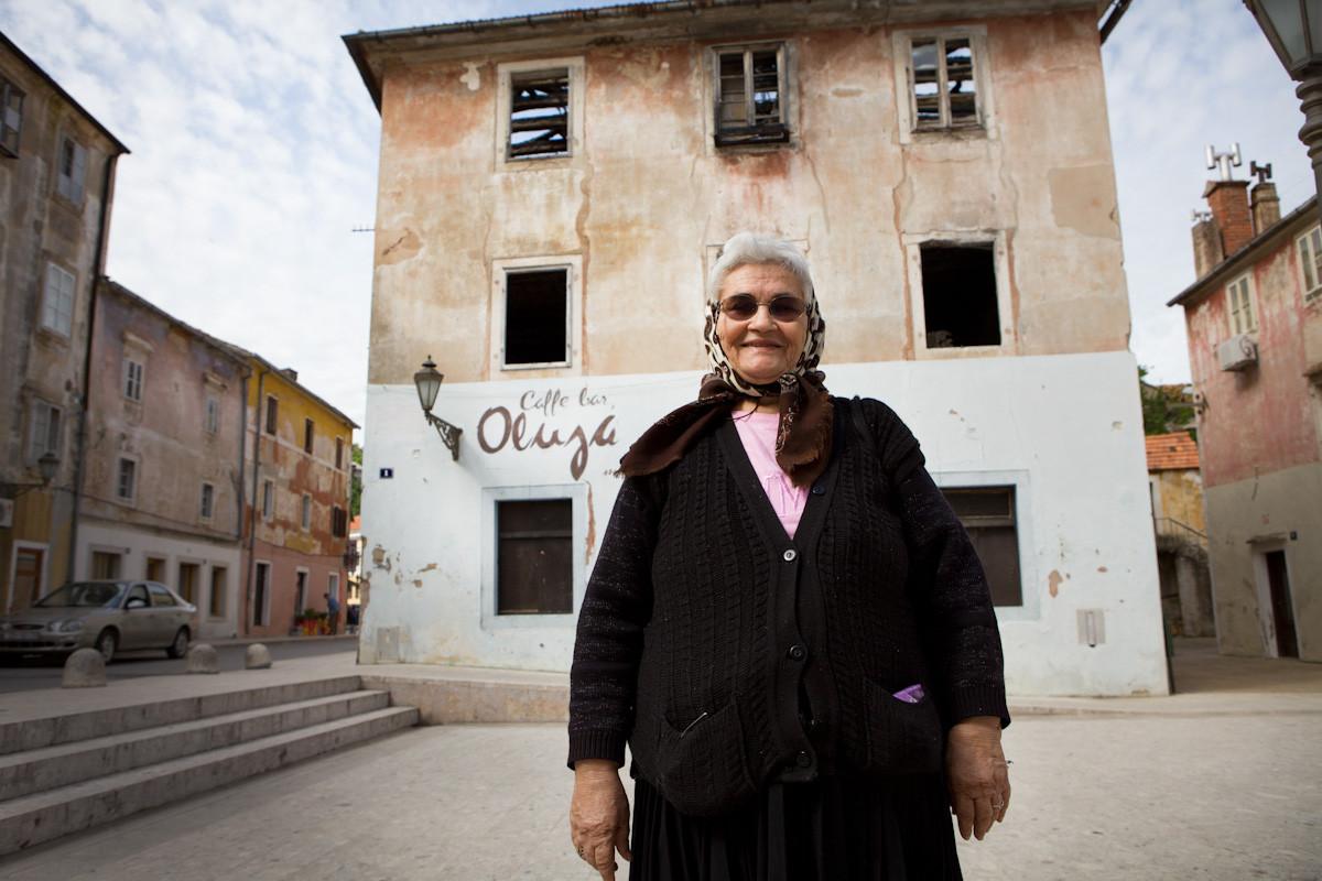 """Ika Milanko teme che entrando in EU diminuisca la pensione, ha 76 anni, 5 figli e 7 nipoti, vive da sola. Davanti al caffè """"Oluja"""" (significa """"Tempesta""""- l'operazione militare dell'esercito croato contro l'esercito Serbo della Krajina), nella piazza di Obrovac, oggi è chiuso per sempre."""