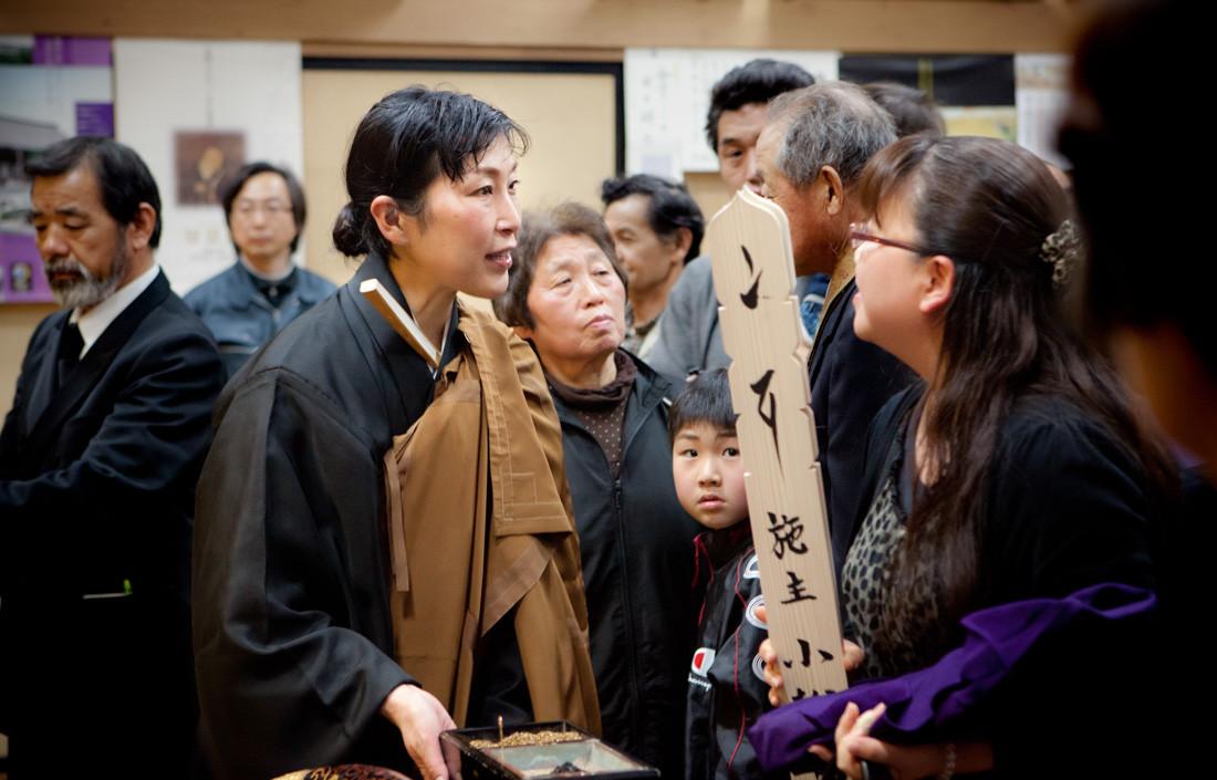 """Una cerimonia detta """"del quarantanovesimo"""", ovvero a quarantanove giorni dalla morte. Un passo significativo secondo la religione buddista. I familiari leggono il sutra ad alta voce per far sentire ai giudici del cancello della sentenza nel cammino dei deceduti per diventare un Buddha, vengono giustificati a seconda del peccato, possono essere condannati all'inferno, ma se sono raggiunti dal lutto della famiglia potrebbero essere perdonati. Nel tempio buddista Jounenji di Kesennuma."""